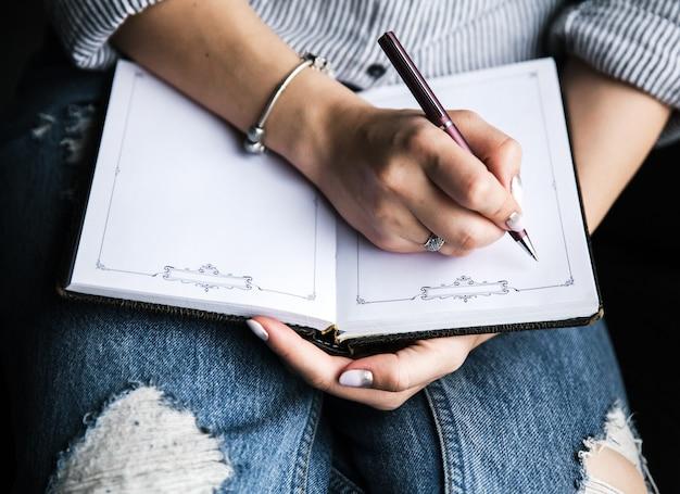 手にノートやスケッチブック。創造性、芸術、教育のコンセプト。トーン画像 Premium写真