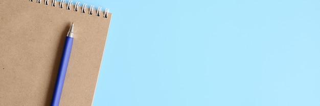 Блокнот или альбом для рисования из крафт-бумаги и ручки на синем фоне. место для текста. знамя Premium Фотографии