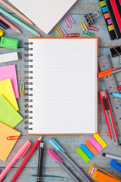 Notebook paper and school or office tools on vintage wood table Free Photo