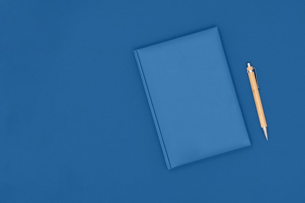 Notebook and pen on blue table. business concept. Premium Photo