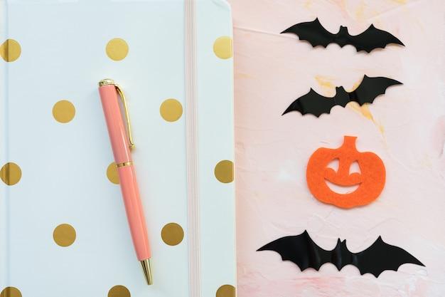 Блокнот, ручка, тыквы и летучие мыши на розовом, плоская планировка Premium Фотографии