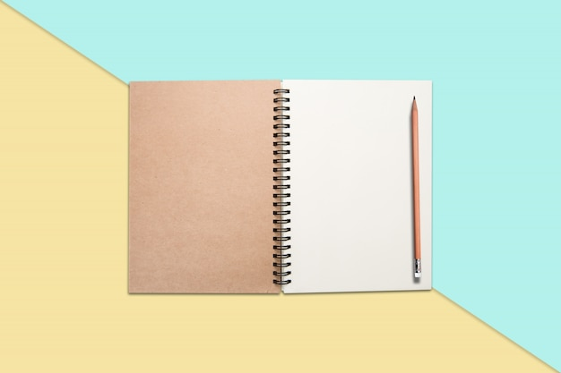 Notebook and pencil on colored background Free Photo