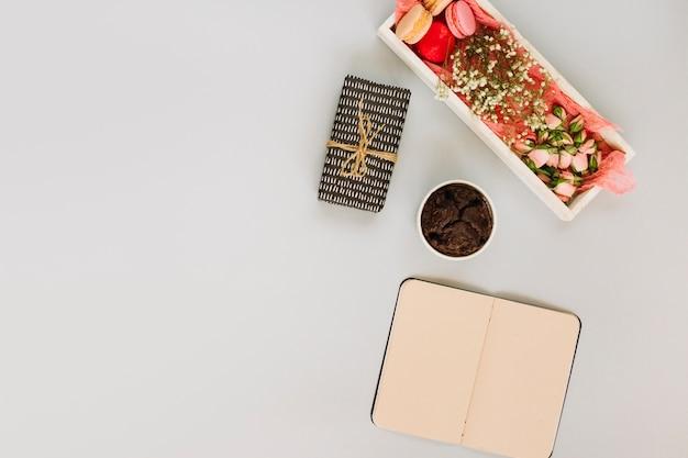 Notebook and present near yummy dessert Free Photo