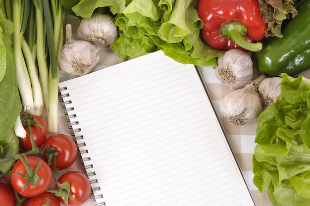 Notebook surrounded by vegetables Free Photo