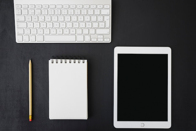 Notebook, tablet and keyboard on dark desk Free Photo
