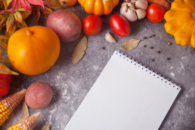 Notebook with autumn leaves and vegetables on the concrete background Premium Photo