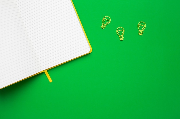 Notebook with blank pages and paperclip light bulb idea on green Premium Photo