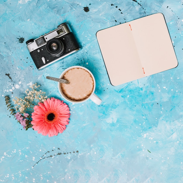 Notebook with camera, coffee and flowers on table Free Photo