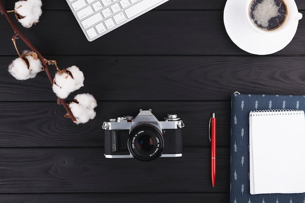 Notebook with camera and coffee on table Free Photo