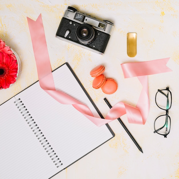 Notebook with camera and ribbon on light table Free Photo