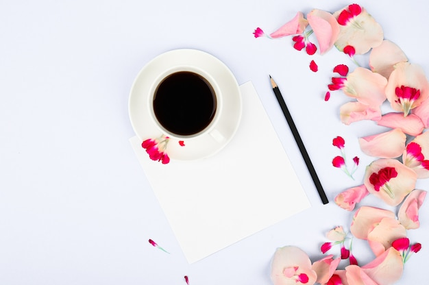 Notebook with clean page, cup of coffee and pink flowers. woman working desk Premium Photo