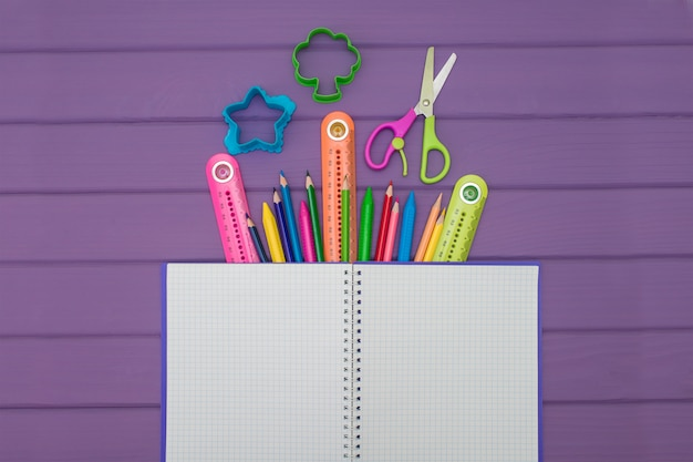 A notebook with colored pencils, rulers and scissors Premium Photo