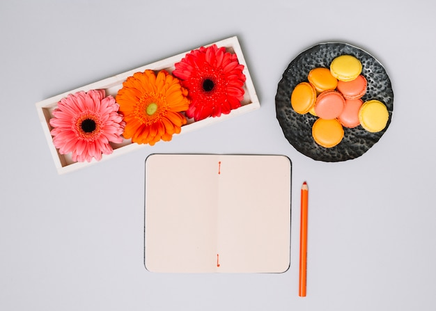 Notebook with cookies and bright flowers on white table Free Photo