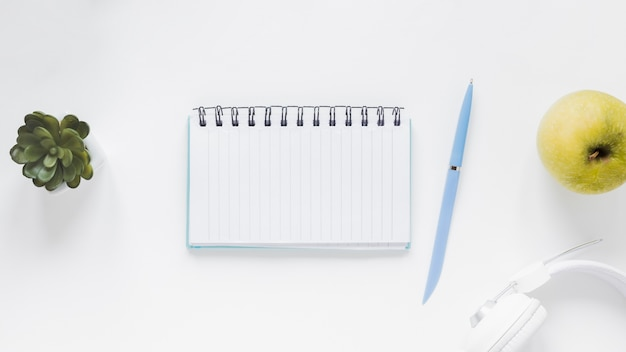 Notebook with pen near apple and headphones on white desk Free Photo