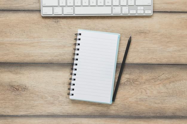 Блокнот с ручкой возле клавиатуры на деревянный стол Бесплатные Фотографии