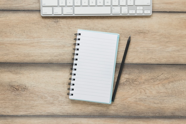 Notebook with pen near keyboard on wooden table Free Photo