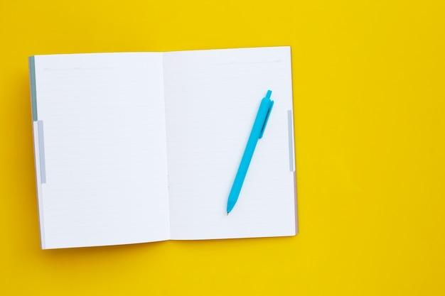 黄色い表面にペンが付いているノート Premium写真