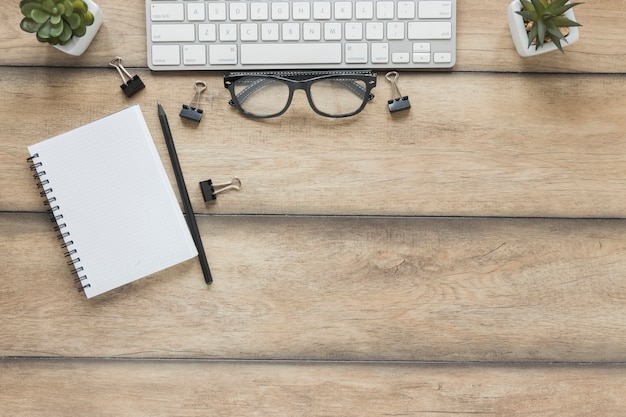 Notebook with pen placed near keyboard and glasses on wooden table Free Photo