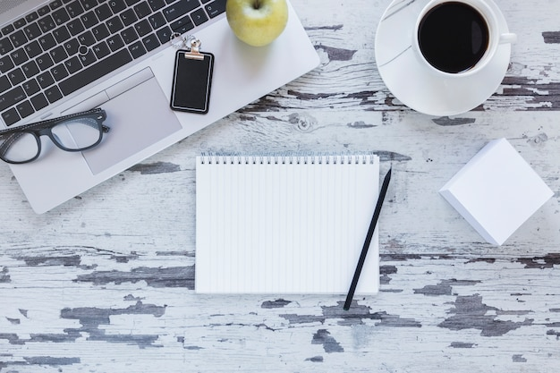 Notebook with pencil near laptop and coffee cup Free Photo