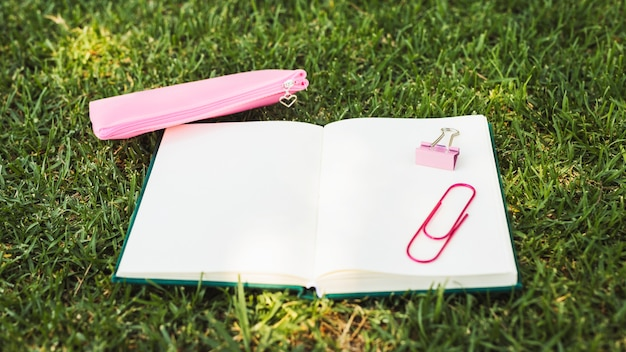 Notebook with pink stationery on grass Free Photo