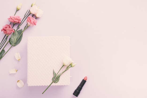 Notebook with rose flowers and lipstick on table Free Photo