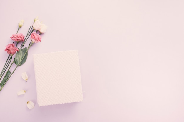 Notebook with rose flowers on table Free Photo
