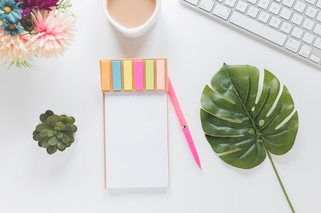 Notebook with stickers near coffee cup, keyboard and plants Free Photo