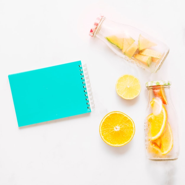 Notebook with turquoise cover lime orange and glass bottles with cut citrus Free Photo