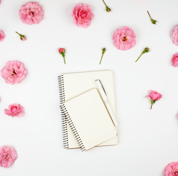 Notebook with white blank pages on purple and pink with petals Premium Photo