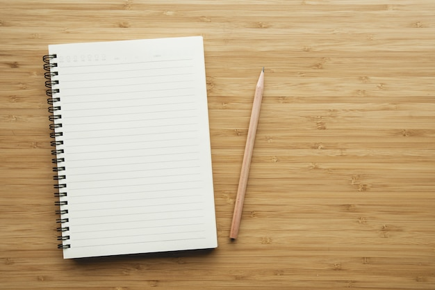 Notebook on wood table background. Premium Photo