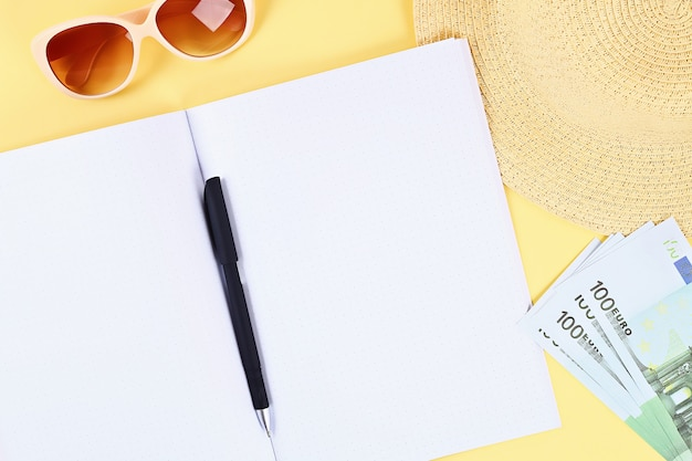 Notebook on a yellow background. summer concept. preparing for vacation. Premium Photo