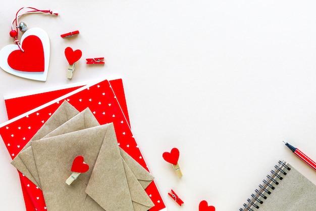 Блокноты и конверты для школы или офиса красного цвета на белом столе с копией пространства. Бесплатные Фотографии