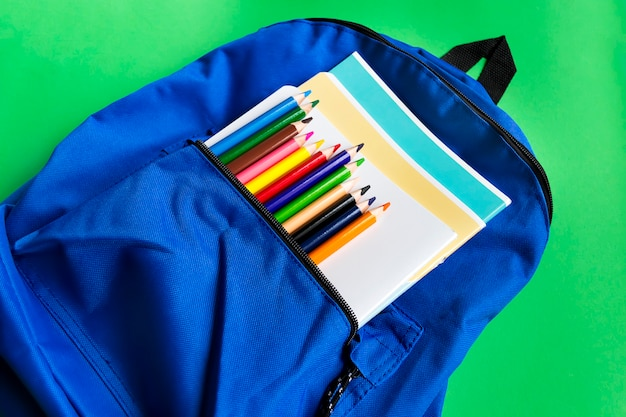 Notebooks and multi-colored pencils in a backpack on a paper green background. school accessories. top view Premium Photo