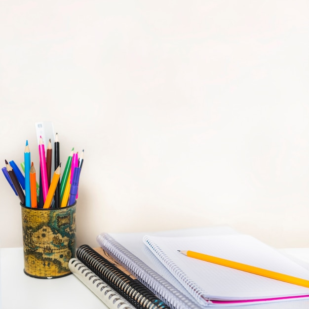 Notebooks near cup with pencils Free Photo