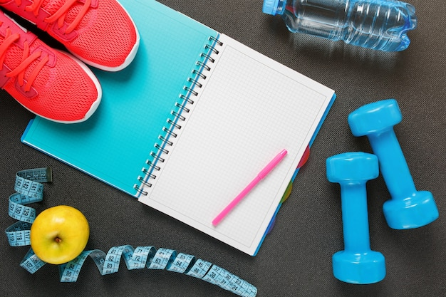 Notepad, a bottle of water, an apple, a skipping rope, dumbbells. healthy diet, lifestyle, concept of dumbbells, exercise Premium Photo