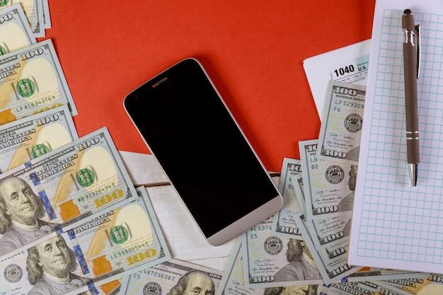 Notepad, cellphone, pen and us dollar bills Premium Photo