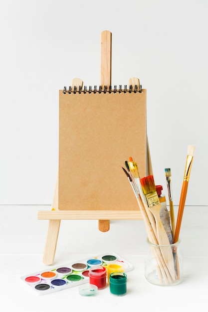 Notepad on easel and paint brushes Free Photo