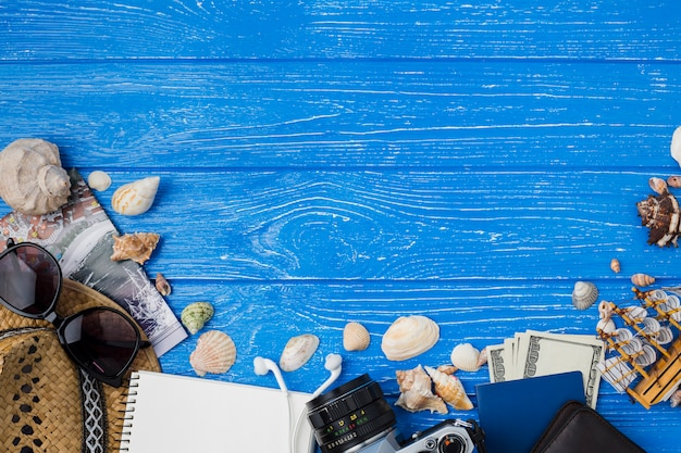 Notepad near hat with earphones and money among seashells and camera Free Photo