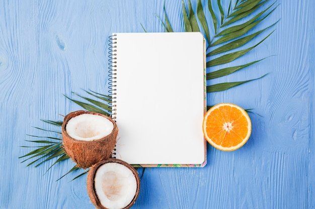 Notepad near plant leaves with fresh coconuts and orange on board Free Photo