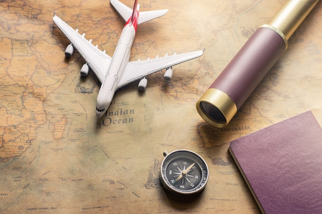 Notepad for note with passport, binoculars, pencil, compass, airplane on paper map for travel adventure discovery image Premium Photo