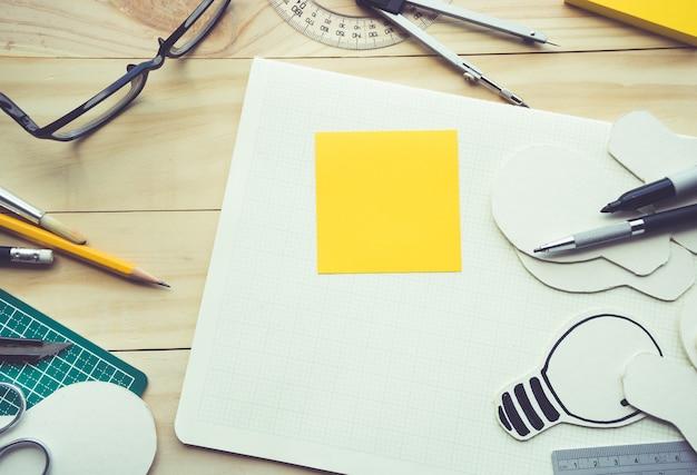 Блокнот на рабочем столе с элементами инструментов, оборудования Premium Фотографии