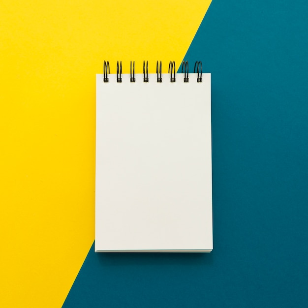 Notepad on yellow and blue background Free Photo