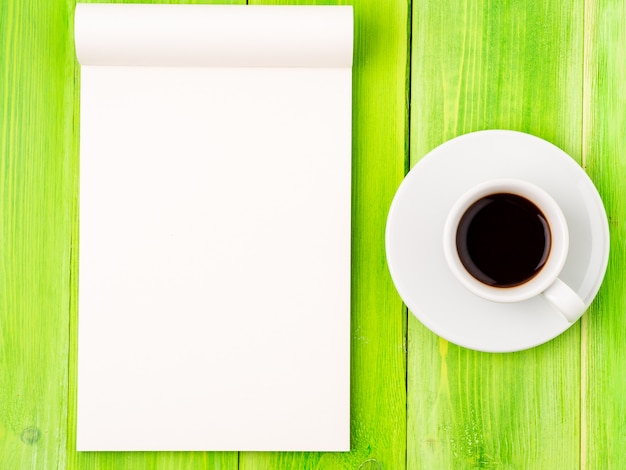 Notepad open with white blank page for writing idea or to-do list, cup of coffee on green wood table Premium Photo