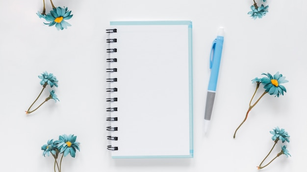 Notepad and pen near blue chamomile flowers Free Photo