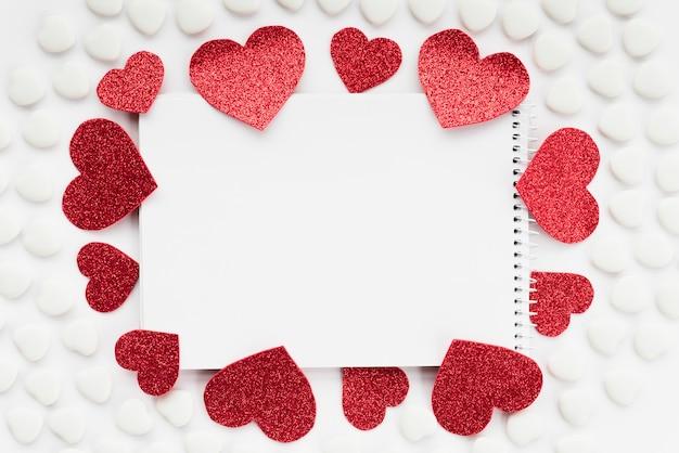 Notepadbetween sets of ornament hearts Premium Photo