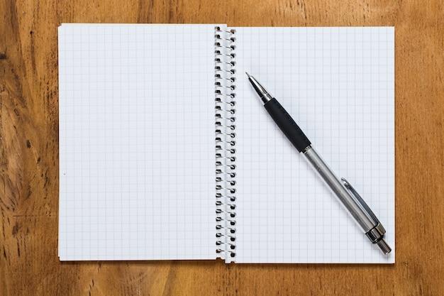 Blocco note sul tavolo con una penna Foto Gratuite