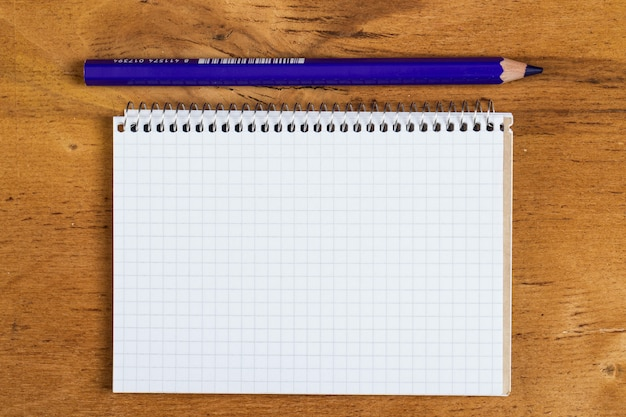 Notepad on the table with a pencil Free Photo