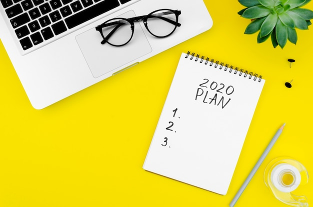 Notepad with 2020 resolutions on yellow background Free Photo