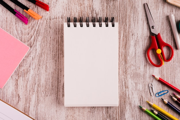 Notepad with drawing set on wooden surface Free Photo