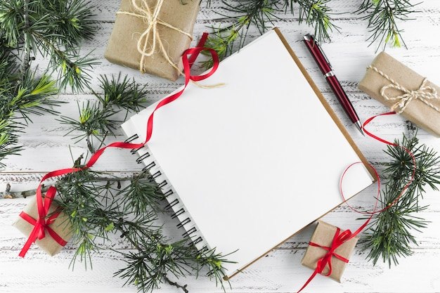 Notepad with fir tree branches on wooden table Free Photo